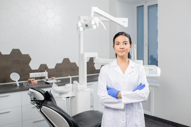 歯科医院でカメラの前に立っている間胸で腕を交差させるホワイトコートと手袋の若い自信を持ってブルネットの女性歯科医