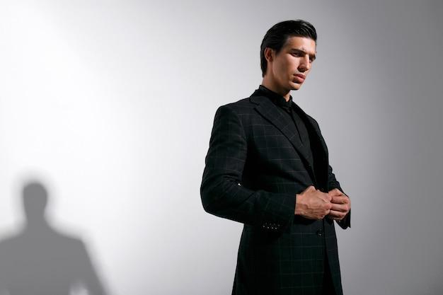 Молодой уверенный человек брюнет в черном стильном костюме на белом фоне. место для текста.