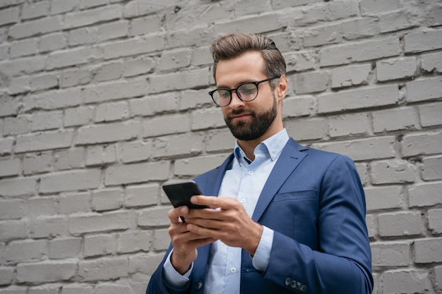 Молодой уверенный бизнесмен, держащий смартфон, общение онлайн, проверка электронной почты на улице