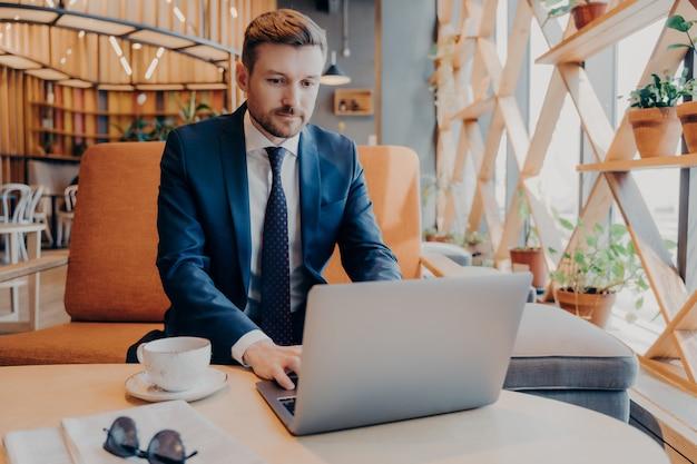 Молодой уверенный в себе бизнесмен в строгом костюме работает онлайн на ноутбуке в холле корпоративного центра во время перерыва на кофе, готовя презентацию для деловой встречи с новыми партнерами
