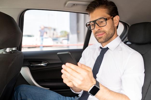 Молодой уверенный бизнесмен в элегантной повседневной одежде сидит в машине и смотрит на экран смартфона во время текстовых сообщений