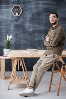 칠판의 배경에 테이블에 서있는 동안 가슴에 팔을 교차 젊은 자신감 사업가 또는 회사원