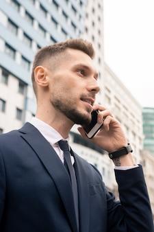 Молодой уверенный бизнесмен разговаривает с клиентом или партнером по смартфону во время движения на работу утром