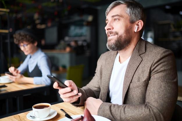 レジャーで快適なカフェのテーブルに座っているスマートフォンで自信を持っての若手実業家
