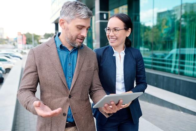 Молодой уверенный бизнесмен с тачпадом обсуждает онлайн-информацию со своим коллегой на ходу