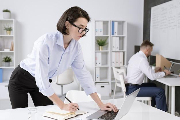 Молодая уверенная деловая женщина наклоняется над столом перед ноутбуком во время работы в сети и делает заметки в офисной среде