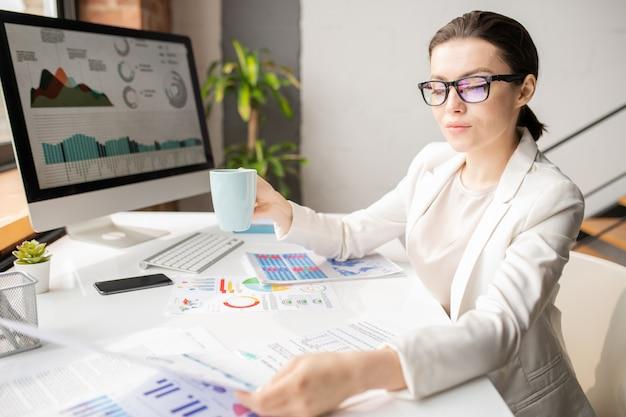 Молодая уверенная бизнес-леди в строгой одежде, пьющая за столом, читая один из финансовых документов
