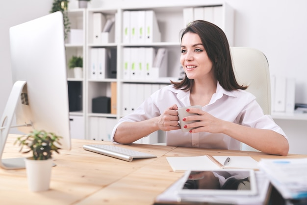 Молодая уверенная деловая женщина с кружкой сидит за столом перед экраном компьютера, пьет чай и разговаривает через видеочат
