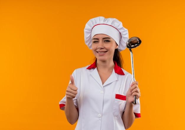La giovane ragazza caucasica sicura del cuoco in uniforme del cuoco unico lampeggia i suoi pollici in su e tiene il mestolo isolato su priorità bassa arancione con lo spazio della copia