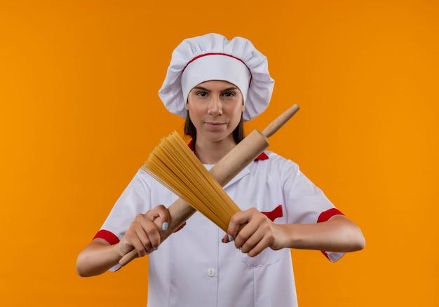 La giovane ragazza caucasica sicura del cuoco in uniforme del cuoco unico attraversa il mattarello e il mazzo di spaghetti isolati sullo spazio arancione con lo spazio della copia