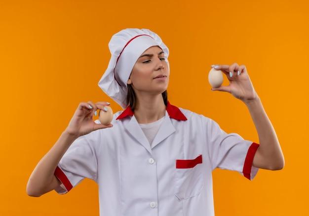 La giovane ragazza caucasica sicura del cuoco in uniforme del cuoco unico tiene ed esamina le uova sull'arancia con lo spazio della copia