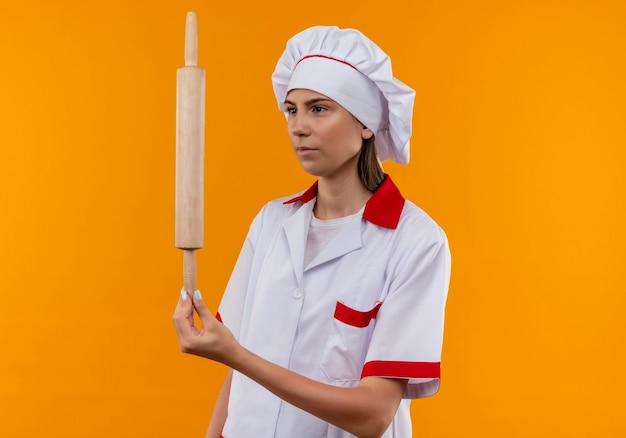 La giovane ragazza caucasica sicura del cuoco in uniforme del cuoco unico tiene ed esamina il mattarello isolato su priorità bassa arancione con lo spazio della copia
