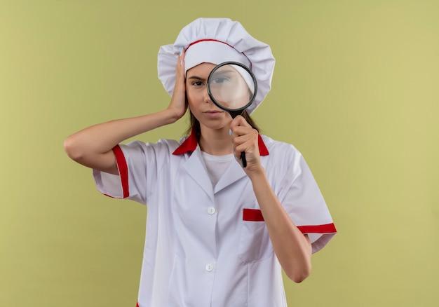 La giovane ragazza caucasica sicura del cuoco in uniforme del cuoco unico tiene la lente d'ingrandimento e mette la mano sulla testa sul verde con lo spazio della copia
