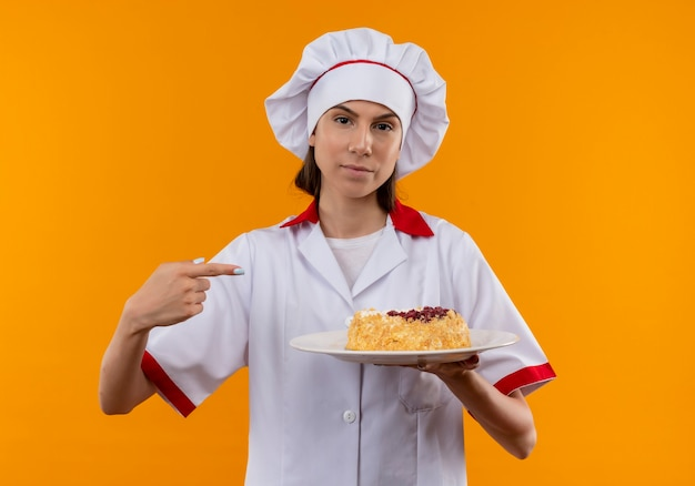La giovane ragazza caucasica sicura del cuoco in uniforme del cuoco unico tiene e punti alla torta sulla zolla isolata su fondo arancio con lo spazio della copia
