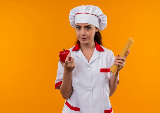 Young confident caucasian cook girl in chef uniform holds red pepper and bunch of spaghetti isolated on orange wall with copy space