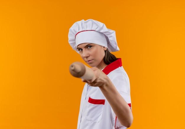 La giovane ragazza caucasica sicura del cuoco in uniforme del cuoco unico tiene il mattarello fuori sull'arancia con lo spazio della copia