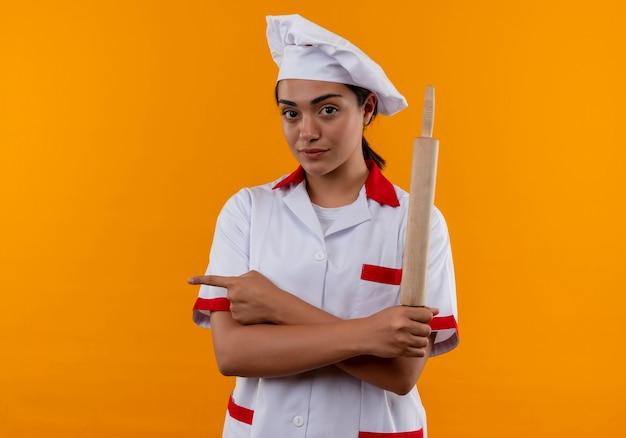 La giovane ragazza caucasica sicura del cuoco in uniforme del cuoco unico tiene il mattarello e indica il lato isolato sulla parete arancione con lo spazio della copia