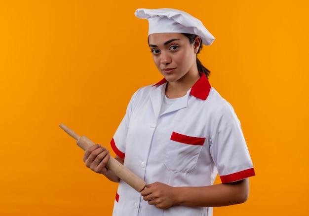 La giovane ragazza caucasica sicura del cuoco in uniforme del cuoco unico tiene il mattarello con entrambe le mani isolate sulla parete arancione con lo spazio della copia