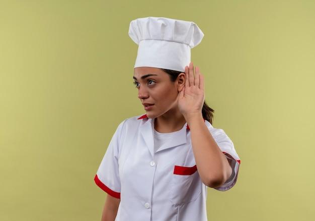 シェフの制服のジェスチャーで若い自信を持って白人料理人の女の子は、コピースペースで緑の壁に分離されたサインを聞くことができません