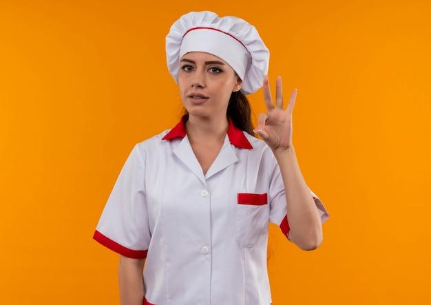シェフの制服のジェスチャーで若い自信を持って白人料理人の女の子はコピースペースでオレンジ色の壁に分離された手のサインok