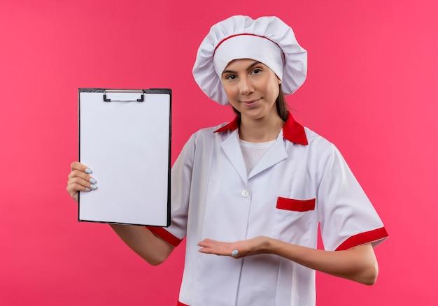 シェフの制服を着た若い自信を持って白人料理人の女の子は、コピースペースとピンクのスペースで隔離クリップボードを保持し、ポイントします