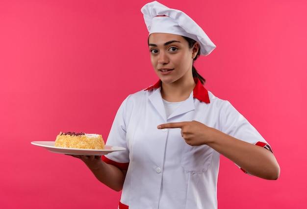Молодая уверенная в себе кавказская девушка-повар в униформе шеф-повара держит торт на тарелке и указывает пальцем на розовую стену с копией пространства