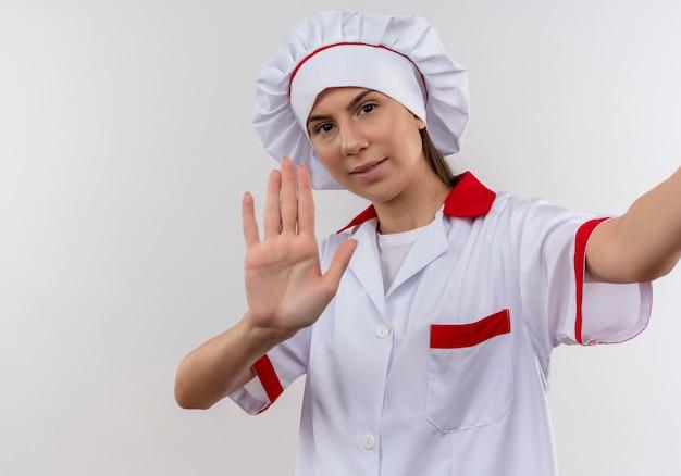 Молодая уверенная кавказская девушка-повар в униформе шеф-повара держит камеру и жестами останавливает знак рукой на белом с копией пространства