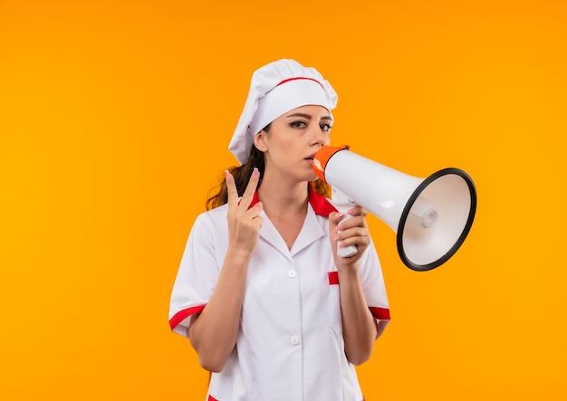 シェフの制服を着た若い自信を持って白人料理人の女の子は大きなスピーカーを保持し、コピースペースでオレンジ色の壁に分離された勝利の手のサインをジェスチャーします
