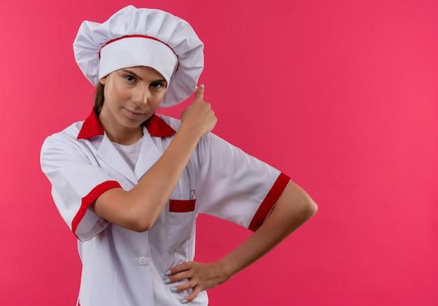 シェフの制服を着た若い自信を持って白人料理人の女の子は、コピースペースとピンクのスペースに分離された