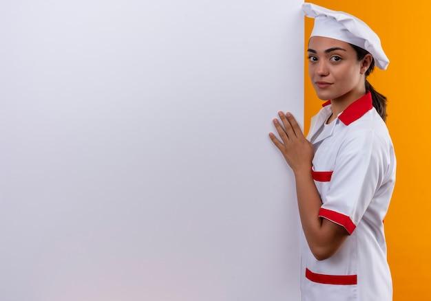 シェフの制服を着た若い自信を持って白人料理人の女の子は白い壁の後ろに立って、コピースペースでオレンジ色の壁に隔離された壁を保持します