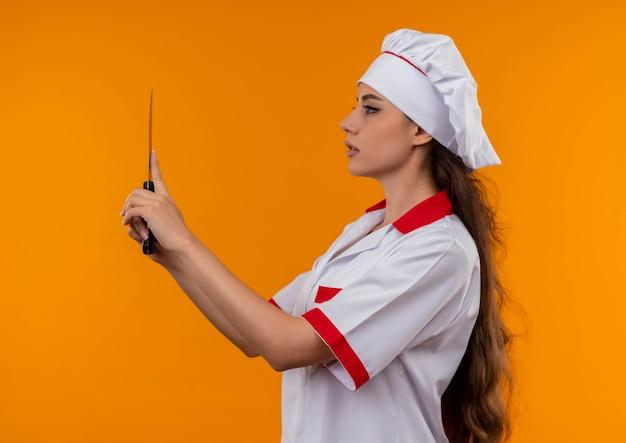 シェフの制服を着た若い自信を持って白人料理人の女の子は横に立って、コピースペースでオレンジ色の壁に分離されたナイフを保持します