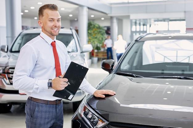 Молодой уверенный в себе кавказский продавец обсуждает автомобиль с покупателями