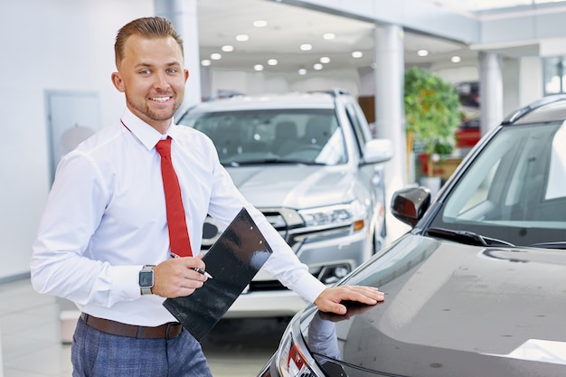 Young confident caucasian salesman discuss auto with buyers