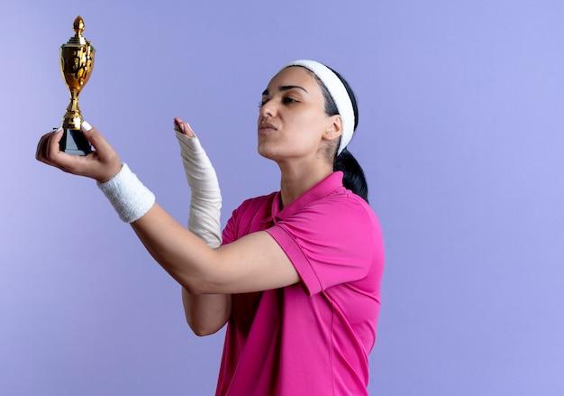 머리띠와 팔찌를 착용하는 젊은 자신감 백인 스포티 한 여자 보유 및 복사 공간 보라색에 우승자 컵에 포인트