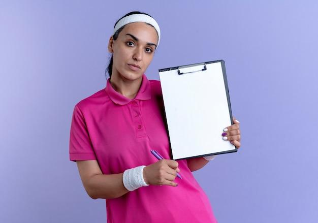 ヘッドバンドとリストバンドを身に着けている若い自信を持って白人のスポーティな女性は、コピースペースと紫色のスペースで隔離ペンとクリップボードを保持