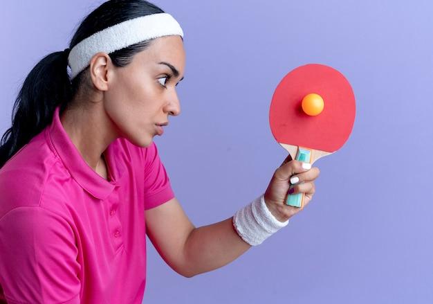 머리띠와 팔찌를 착용하는 젊은 자신감 백인 스포티 한 여자는 복사 공간이 보라색 공간에 고립 탁구 라켓과 공을 보유하고