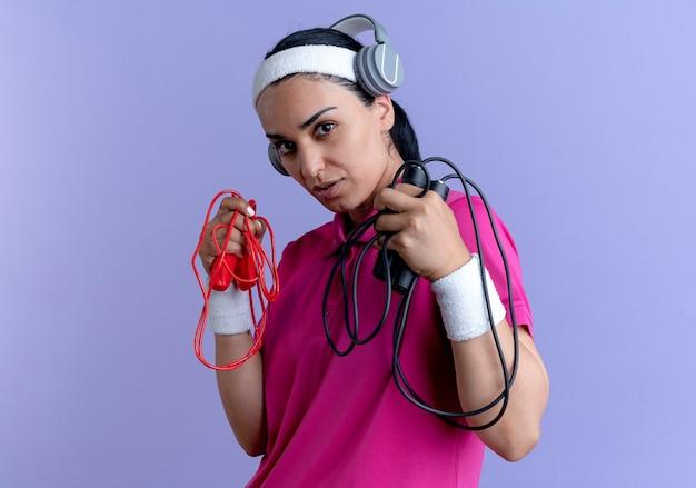 ヘッドフォンでヘッドバンドとリストバンドを身に着けている若い自信を持って白人のスポーティな女性は、コピースペースで紫色の背景に分離された縄跳びを保持します。