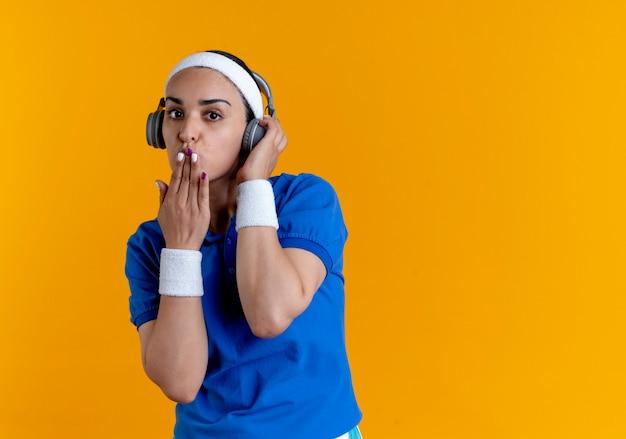 ヘッドフォンでヘッドバンドとリストバンドを身に着けている若い自信を持って白人のスポーティな女性は、コピースペースでオレンジ色の手でキスを送信します