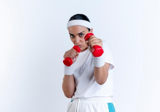 Молодая уверенная в себе кавказская спортивная женщина с повязкой на голову и браслетами делает вид, что защищает, держа гантели, изолированные на белом пространстве с копией пространства