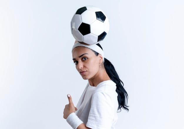 ヘッドバンドとリストバンドを身に着けている若い自信を持って白人のスポーティな女性は横向きに立って頭の上にボールを保持し、コピースペースで白い背景で隔離の親指を立てる