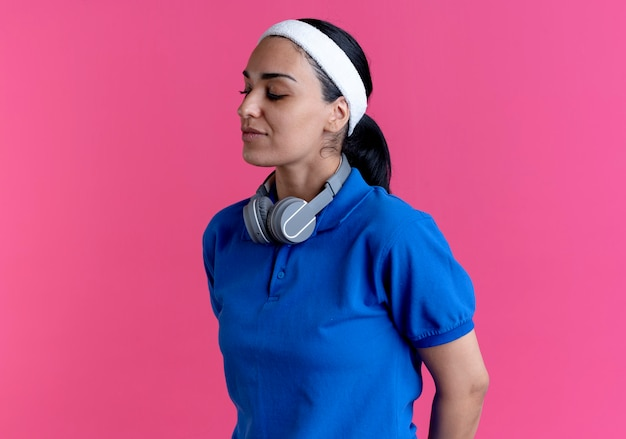 ヘッドバンドとリストバンドを身に着けている若い自信を持って白人のスポーティな女性は、コピースペースでピンクの背景に分離された首にヘッドフォンで立っています
