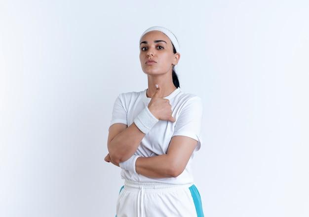 La giovane donna sportiva caucasica fiduciosa che indossa la fascia ed i braccialetti attraversa le braccia ed i pollici in su isolati su spazio bianco con lo spazio della copia