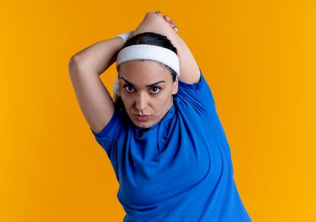La giovane donna sportiva caucasica fiduciosa che indossa la fascia e i braccialetti tiene il braccio dietro la schiena isolato su priorità bassa arancione con lo spazio della copia