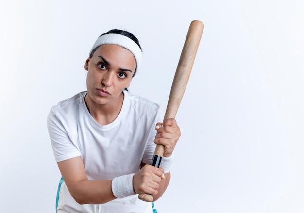 Giovane donna sportiva indoeuropea fiduciosa che indossa fascia e braccialetti tiene la mazza guardando la fotocamera