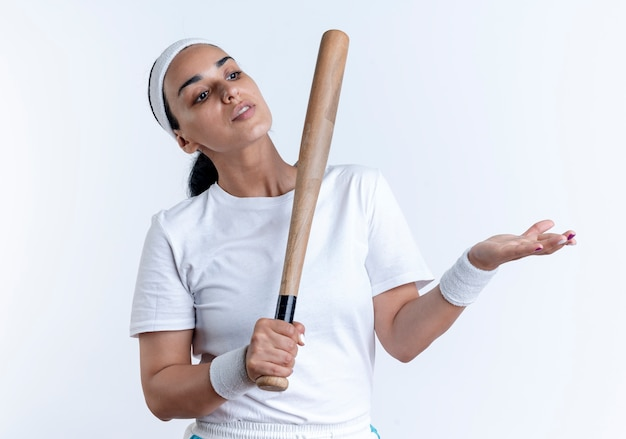 Young confident caucasian sporty woman wearing headband and wristbands holds bat looking and pointing at side isolated on white space with copy space