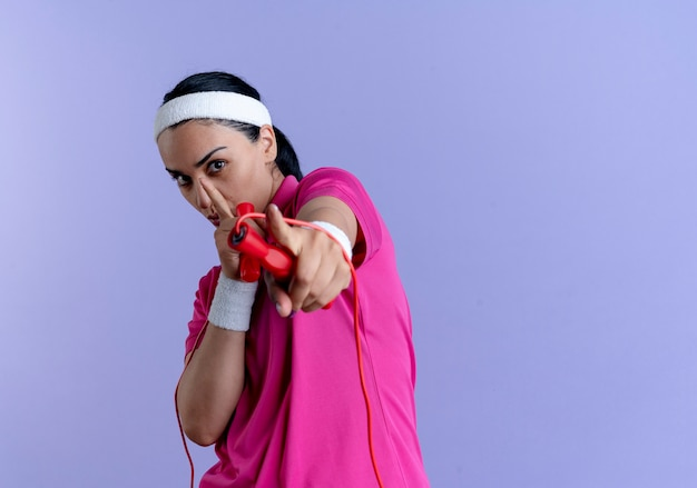 Young confident caucasian sporty woman wearing headband and wristbands holds jumping rope and points at camera