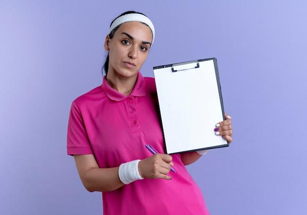 Young confident caucasian sporty woman wearing headband and wristbands holds pen and clipboard isolated on purple space with copy space