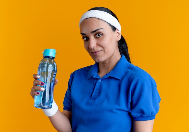 La giovane donna sportiva caucasica fiduciosa che indossa la fascia e i braccialetti tiene la bolletta dell'acqua sull'arancio con lo spazio della copia