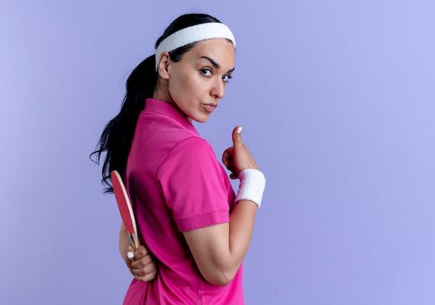 Giovane donna sportiva caucasica fiduciosa che indossa la fascia e braccialetti si trova lateralmente tenendo la racchetta dietro e il pollice in alto su viola con spazio di copia