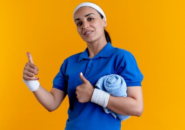 La giovane donna sportiva caucasica fiduciosa che indossa la fascia e i braccialetti thumbs up che tiene l'asciugamano con il braccio sull'arancio con lo spazio della copia